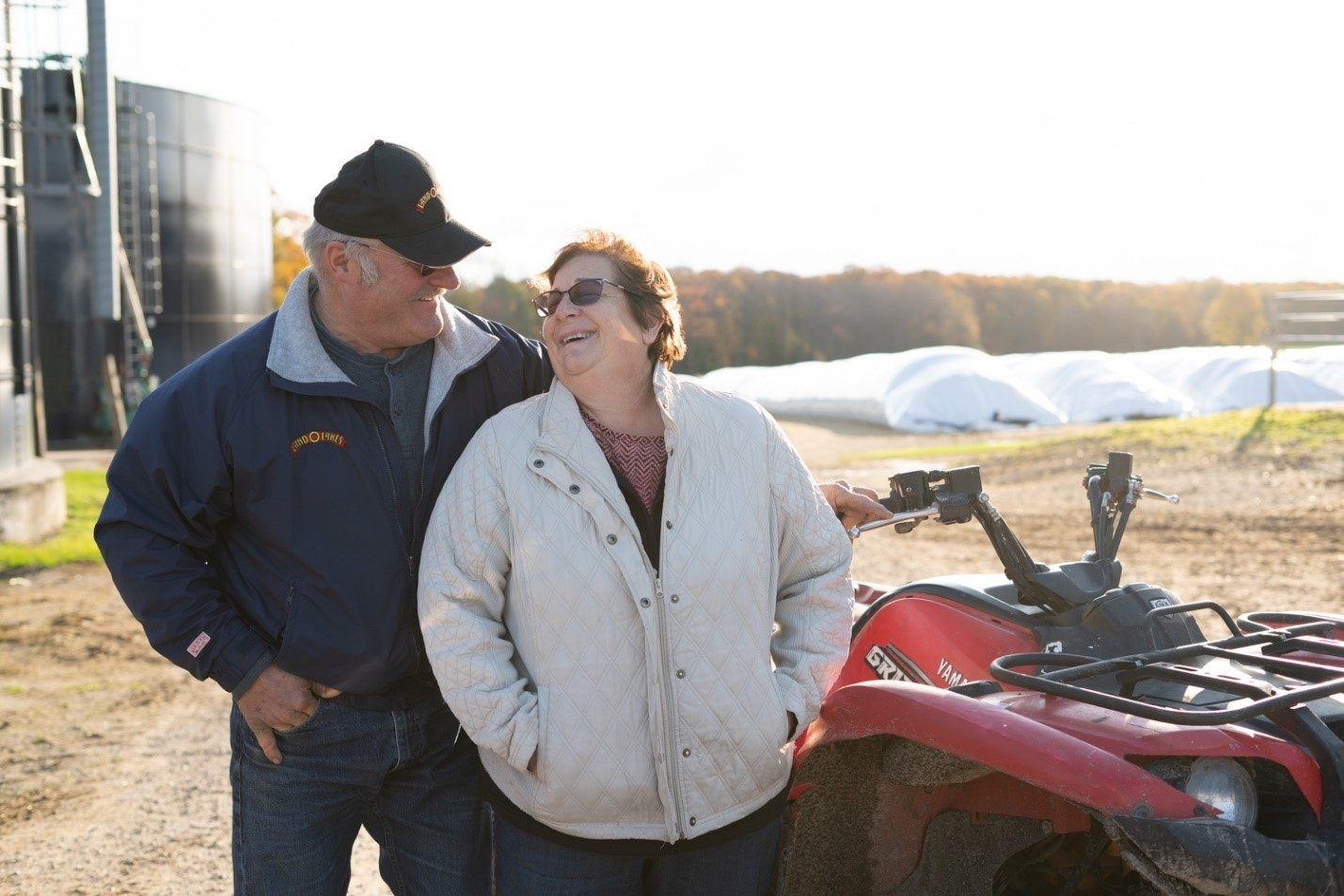 Photo of Deb and Ed Staats, with farm in background