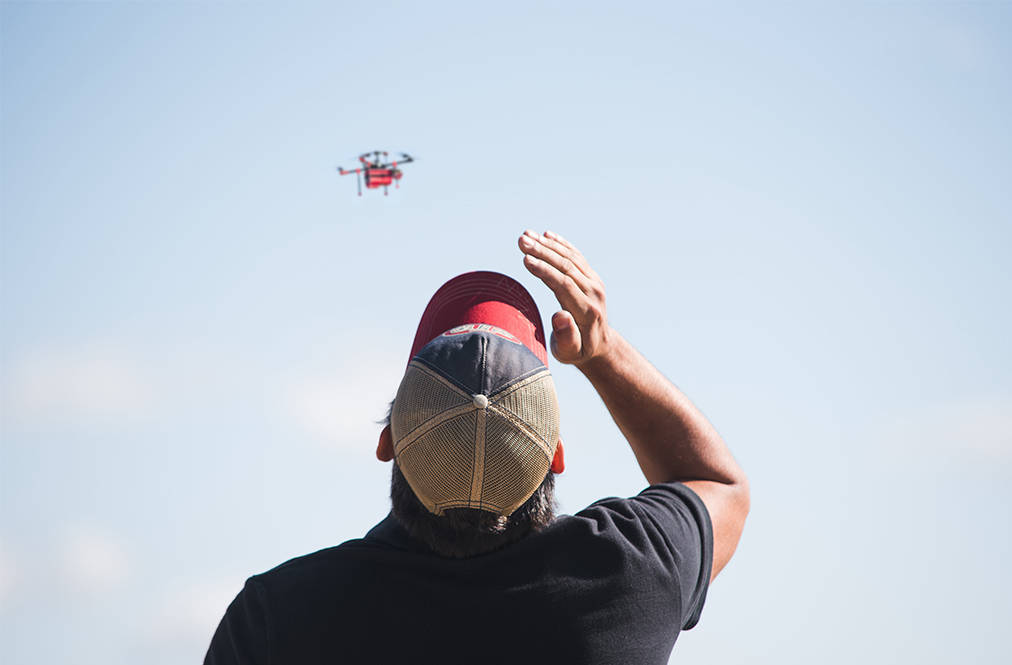 A Farmer Looking At A Drone In The Sky