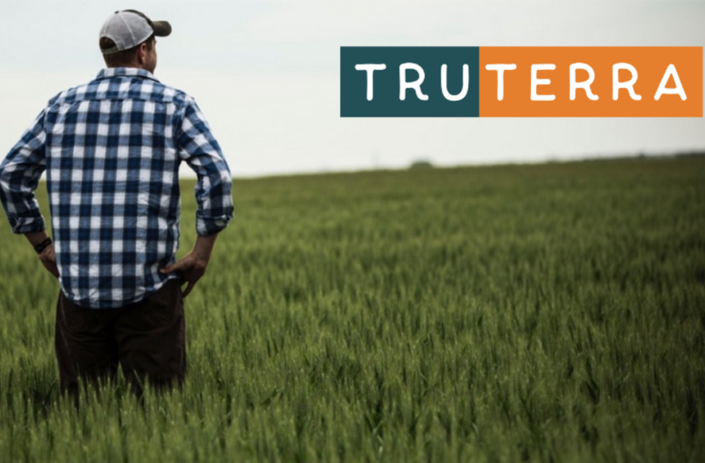 Truterra Logo Over A Farmer In A Field