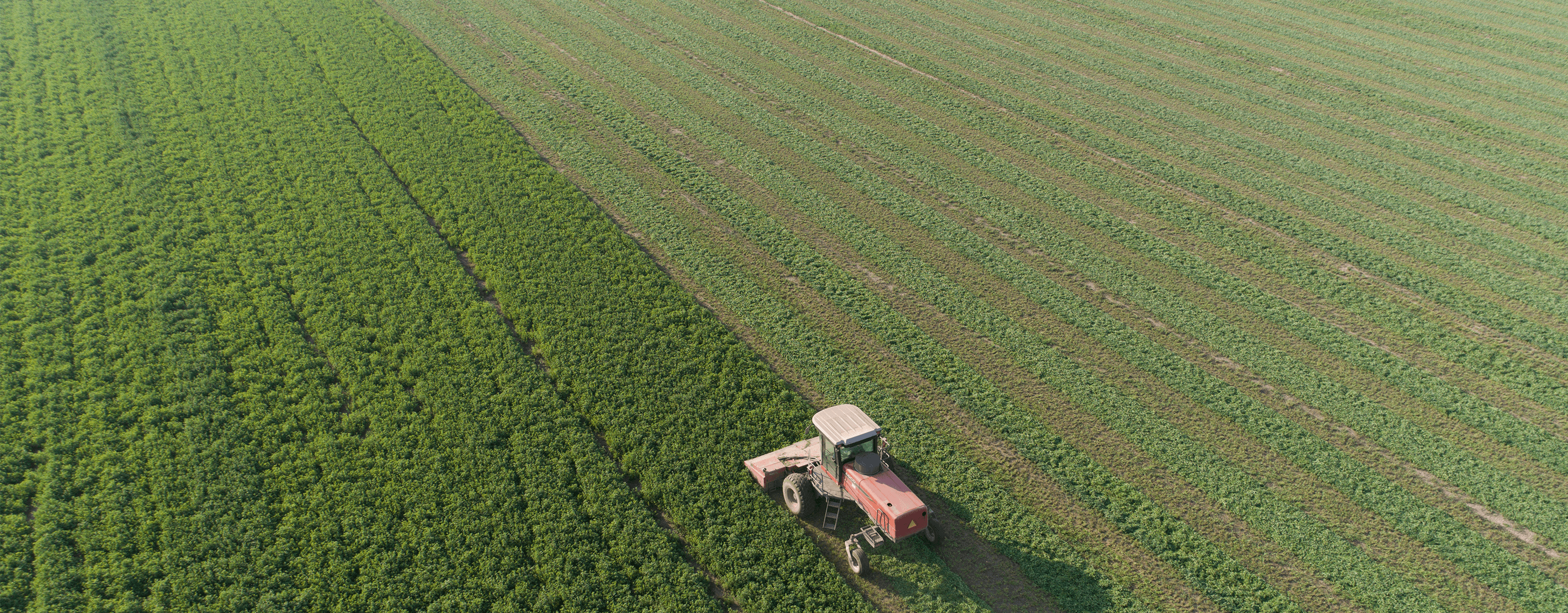 An Aerial View Of A Tractor In The Field Harvesting