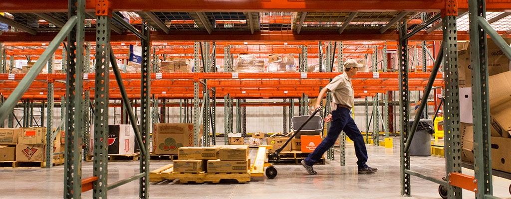 A Worker Moving Pallets Of Donated Food In A Warehouse